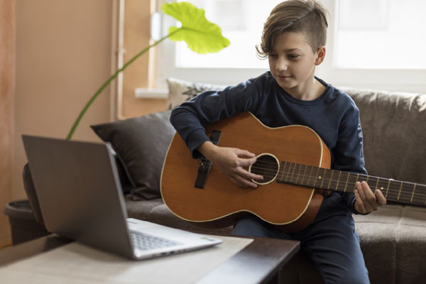 Boy having online guitar lessons
