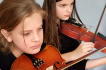 Two girls having violin lessons.